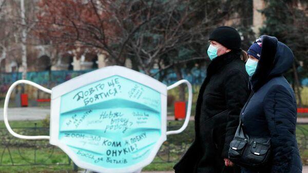 Женщины проходят мимо инсталляции в виде защитной маски на улице в Киеве