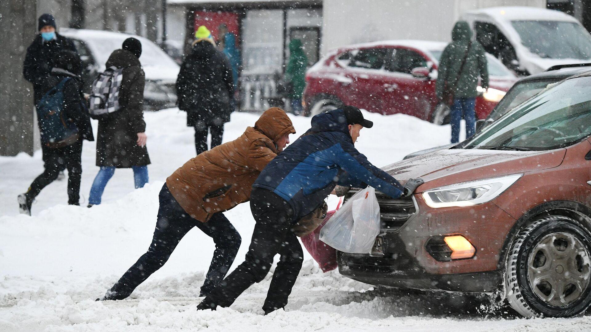Мужчины толкают машину, застрявшую на дороге во время снегопада - РИА Новости, 1920, 21.01.2021