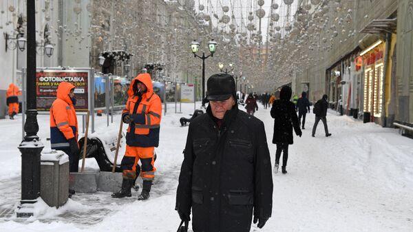Сотрудники коммунальных служб на заснеженной Никольской улице в Москве