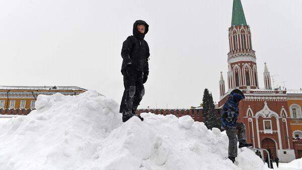 Дети играют на снежной горке на Красной площади в Москве