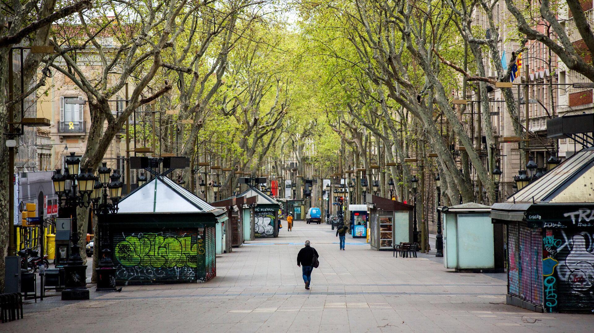 Мужчина в защитной маске идет по пустой пешеходной улице Рамбла в центре Барселоны - РИА Новости, 1920, 14.07.2021