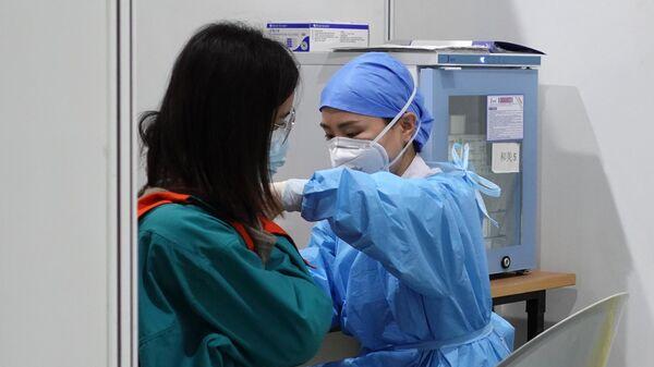 Медицинский работник во время вакцинации пациента от коронавируса в Пекине
