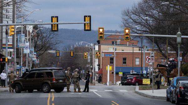 Военнослужащие Национальной гвардии и полиции дежурят на одной из улиц неподалеку от здания Капитолия штата Пенсильвания в Гаррисберге