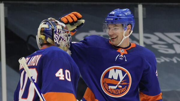UNIONDALE, NEW YORK - JANUARY 18: Semyon Varlamov #40 and Scott Mayfield #24 of the New York Islanders celebrate a 1-0 shutout against the Boston Bruins at the Nassau Coliseum on January 18, 2021 in Uniondale, New York.   Bruce Bennett/Getty Images/AFP