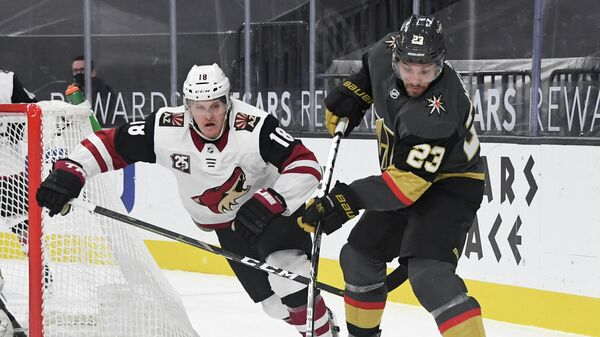 LAS VEGAS, NEVADA - JANUARY 18: Alec Martinez #23 of the Vegas Golden Knights clears the puck under pressure from Christian Dvorak #18 of the Arizona Coyotes in the third period of their game at T-Mobile Arena on January 18, 2021 in Las Vegas, Nevada. The Golden Knights defeated the Coyotes 4-2.   Ethan Miller/Getty Images/AFP