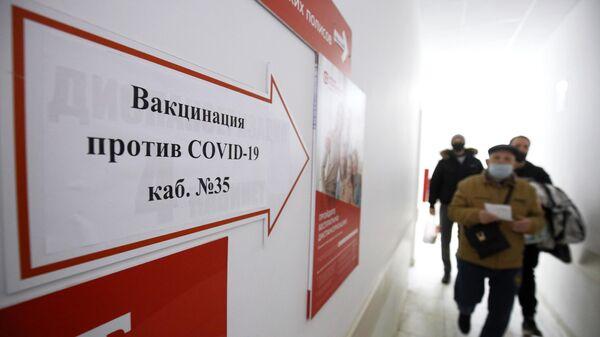 Информационный указатель о массовой вакцинации от коронавируса вакциной Спутник-V (Гам-КОВИД-Вак) на стенде в Динской центральной районной больнице