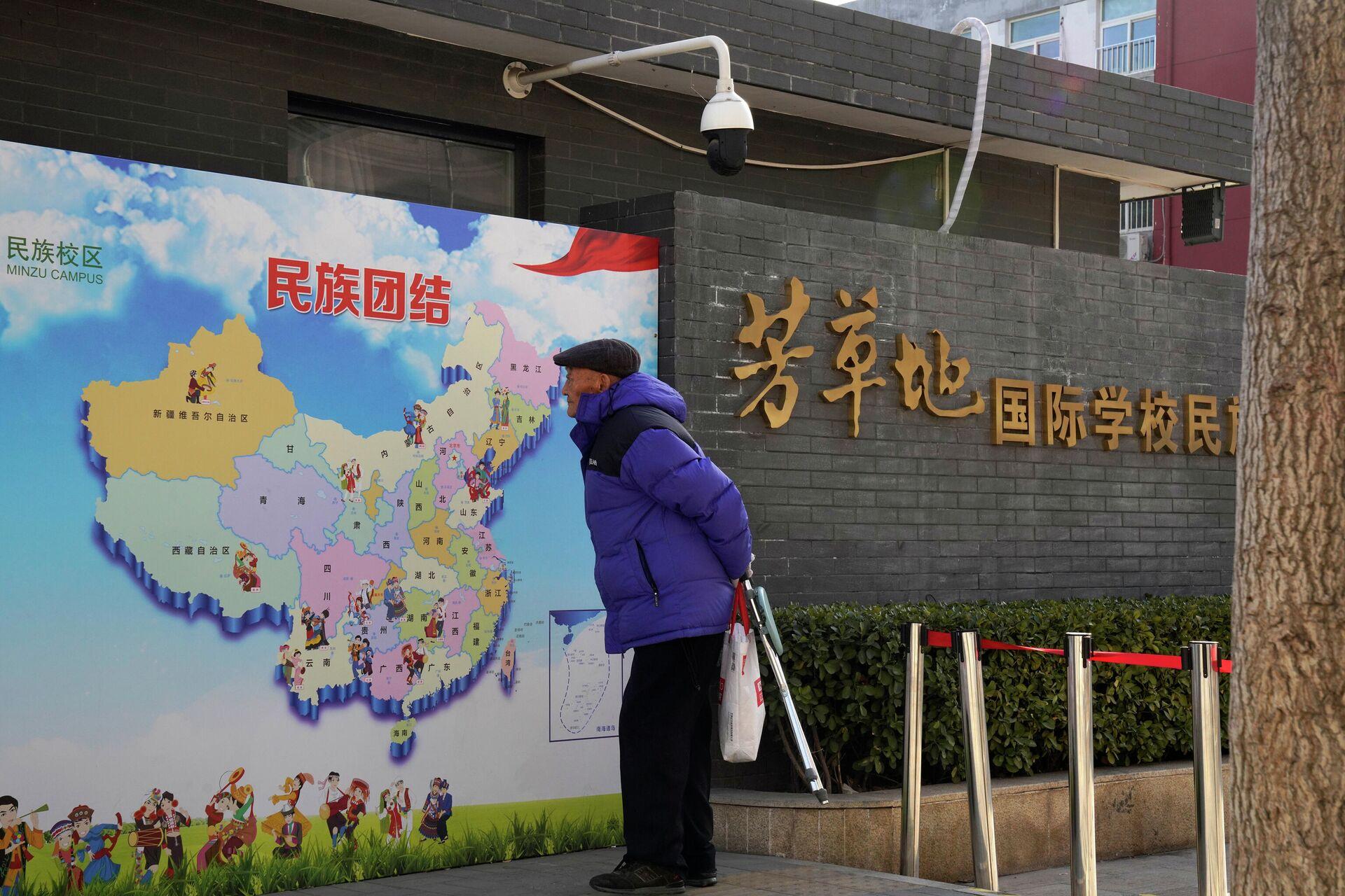 Мужчина рассматривает карту Китая с изображением различных этнических групп в Пекине - ПРОФИ Новости, 1920, 21.01.2021