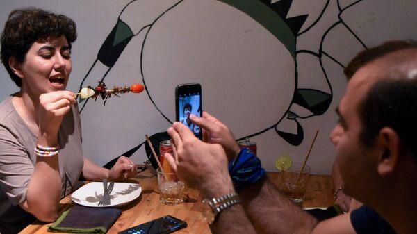 Посетительница ресторана Bugs Cafe со сверчком на шпажке