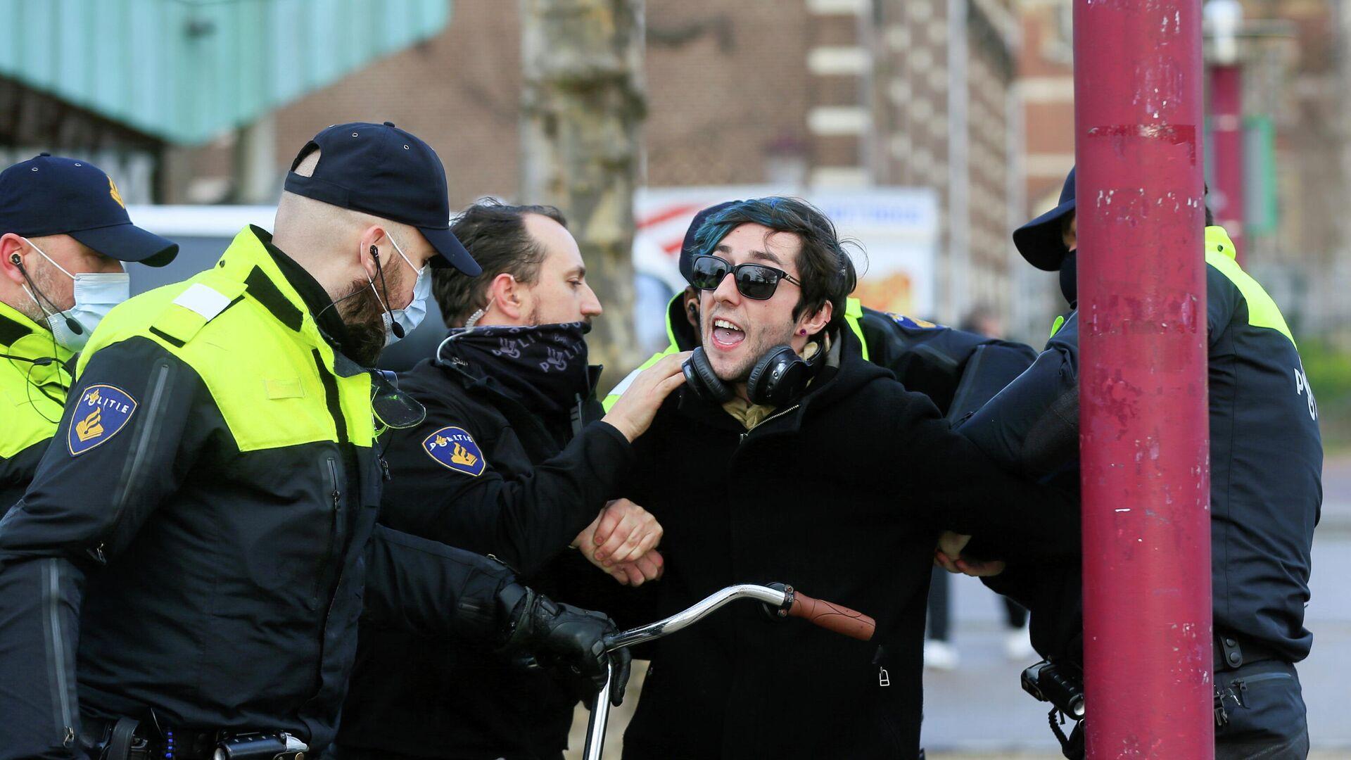 Полицейские во время задержания участника акции протеста против ограничений, введенных для сдерживания распространения коронавируса в Амстердаме - РИА Новости, 1920, 28.01.2021