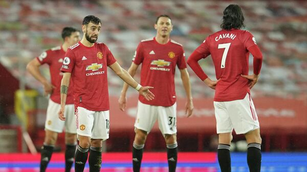 Manchester United's Portuguese midfielder Bruno Fernandes (L) and teammates react after conceding their second goal during the English Premier League football match between Manchester United and Sheffield United at Old Trafford in Manchester, north west England, on January 27, 2021. (Photo by Dave Thompson / POOL / AFP) / RESTRICTED TO EDITORIAL USE. No use with unauthorized audio, video, data, fixture lists, club/league logos or 'live' services. Online in-match use limited to 120 images. An additional 40 images may be used in extra time. No video emulation. Social media in-match use limited to 120 images. An additional 40 images may be used in extra time. No use in betting publications, games or single club/league/player publications. /