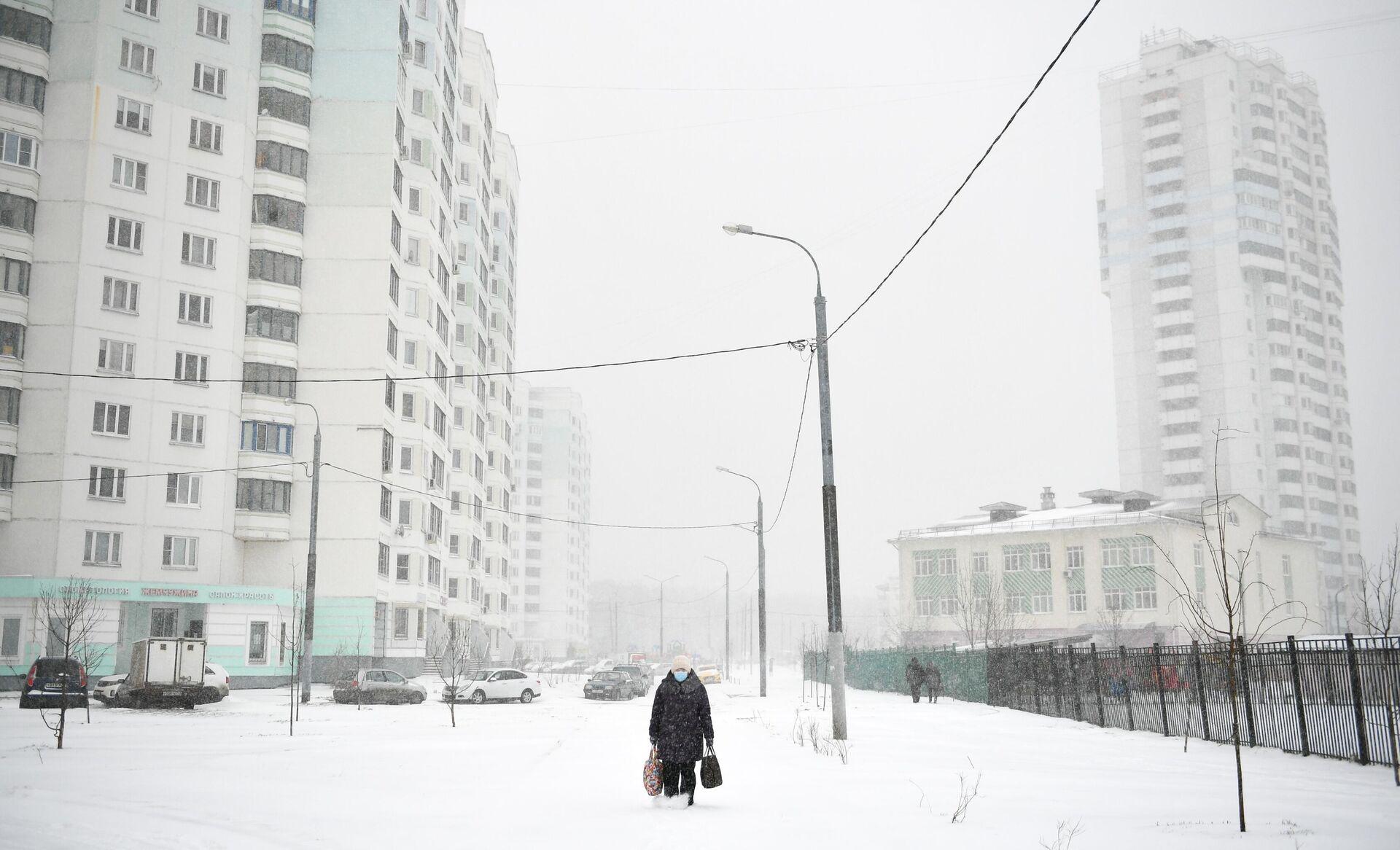 Женщина в защитной маске во дворе жилого дома во время снегопада - РИА Новости, 1920, 28.01.2021