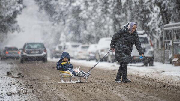 Женщина с ребенком переходит дорогу
