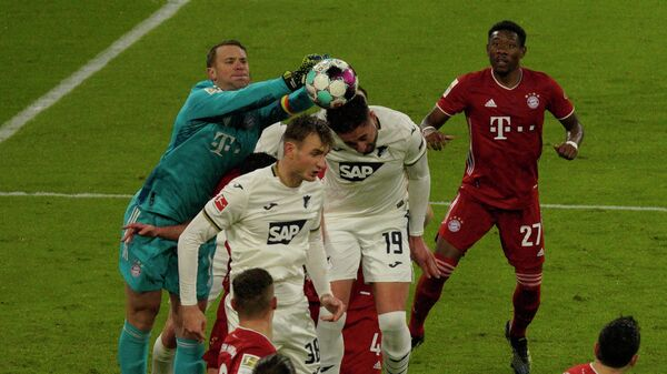 Bayern Munich's German goalkeeper Manuel Neuer (L) jumps to save the ball during the German first division Bundesliga football match FC Bayern Munich v TSG 1899 Hoffenheim in Munich, southern Germany on January 30, 2021. (Photo by GUENTER SCHIFFMANN / various sources / AFP) / DFL REGULATIONS PROHIBIT ANY USE OF PHOTOGRAPHS AS IMAGE SEQUENCES AND/OR QUASI-VIDEO