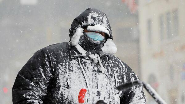 Работник чистит снег во время снегопада в Нью-Йорке