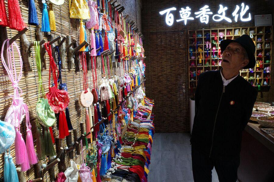Мужчина в сувенирном магазине на одной из улиц города Пинъяо