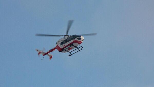 Медицинский вертолет в небе недалеко от места пожара в жилом доме в поселке Мосрентген в Новой Москве