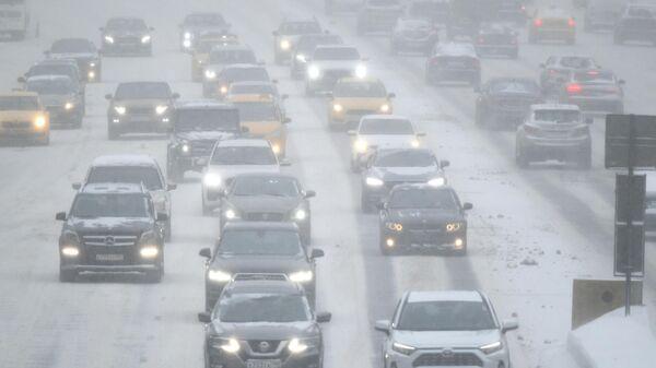 Автомобили на улице Москвы во время снегопада