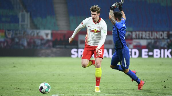 Leipzig's Norwegian forward Alexander Sorloth (L) and Augsburg's Polish goalkeeper Rafal Gikiewicz vie for the ball during the German first division Bundesliga football match between RB Leipzig and FC Augsburg in Leipzig, eastern Germany, on February 12, 2021. (Photo by ANNEGRET HILSE / POOL / AFP) / DFL REGULATIONS PROHIBIT ANY USE OF PHOTOGRAPHS AS IMAGE SEQUENCES AND/OR QUASI-VIDEO