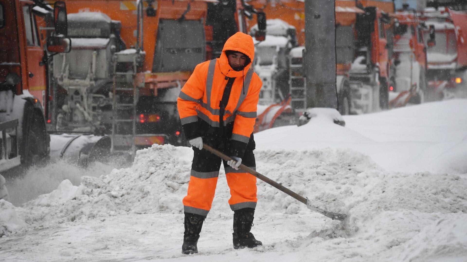 Сотрудник коммунальной службы убирает снег на улице в Москве во время снегопада. - РИА Новости, 1920, 15.02.2021
