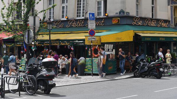 Горожане и туристы на улице Rue du Petit Pont рядом с пабом Cafe Le Petit Pont в Париже