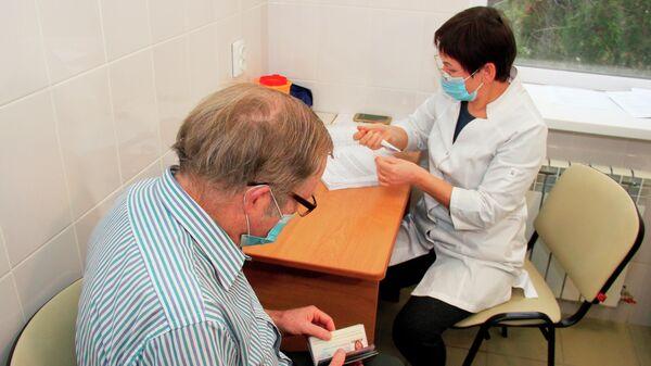 Гражданин США Брюс Уотс Бевен оформляет документы для вакцинации от коронавируса российской вакциной Спутник V (Гам-КОВИД-Вак) в поликлинике в Евпатории