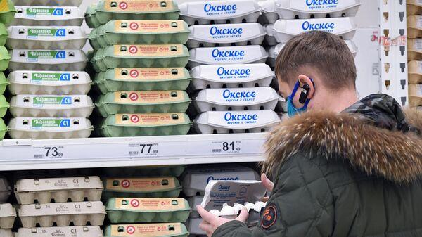 Покупатель выбирает упаковку с яйцами в гипермаркете Ашан в Москве