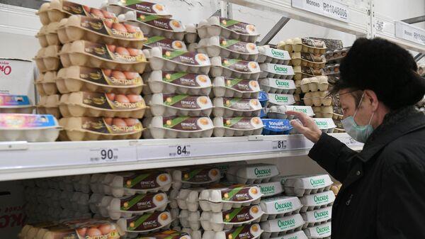 Покупатель выбирает упаковку с яйцами