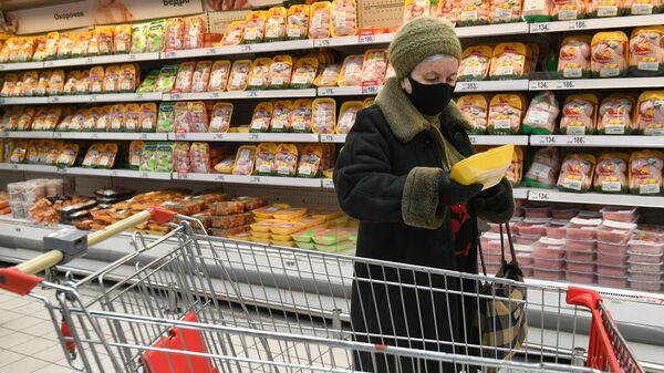 Покупательница выбирает курицу в мясном отделе гипермаркета Ашан в Москве