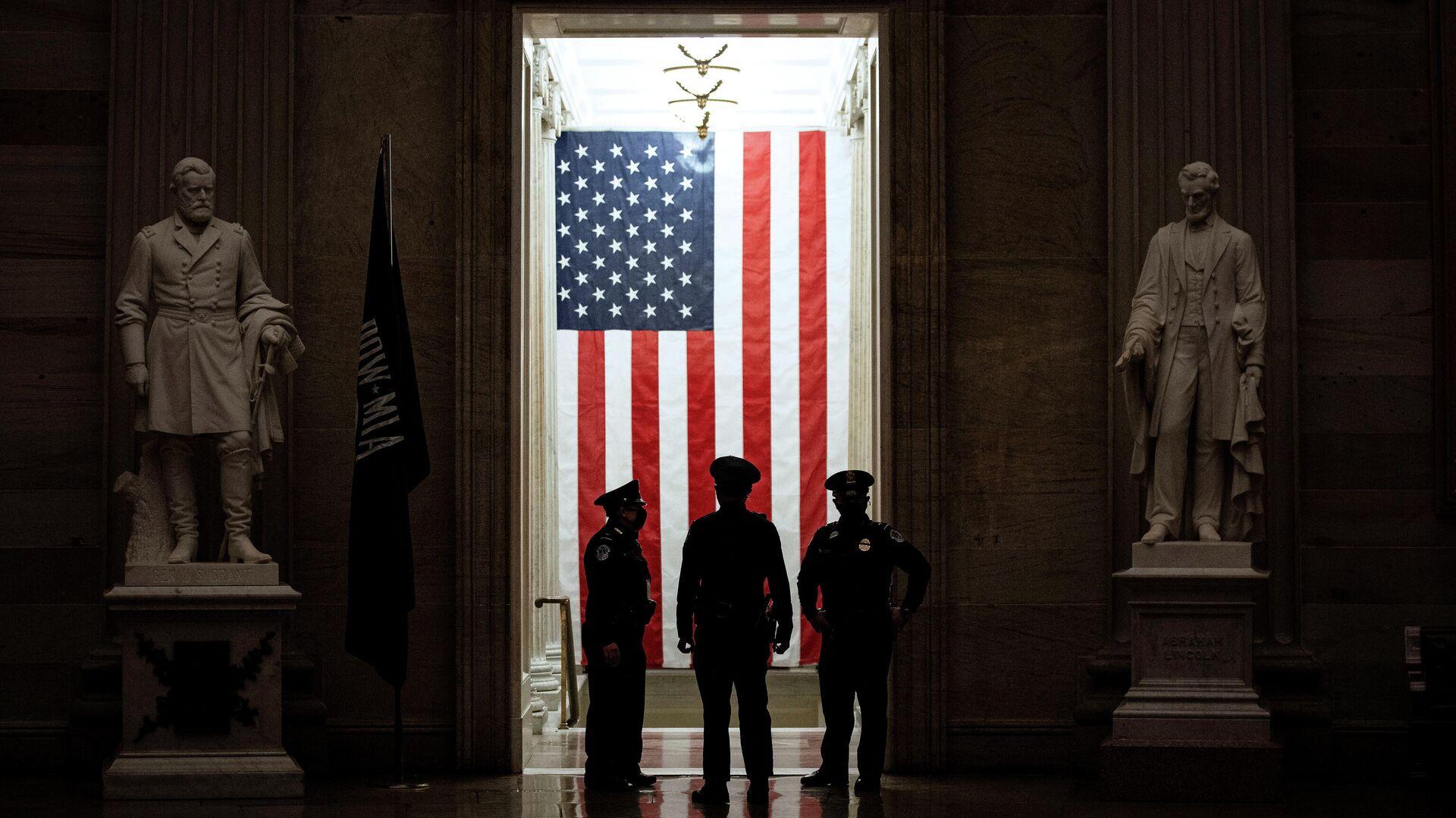 Офицеры полиции стоят перед американским флагом в ротонде Капитолия США в Вашингтоне - РИА Новости, 1920, 02.03.2021
