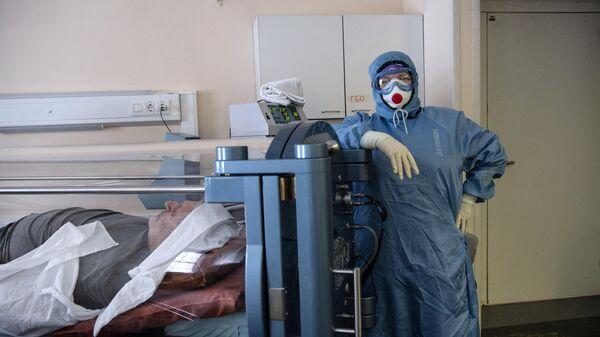 Медицинский работник и пациент c COVID-19, находящийся в барокамере, в НИИ скорой помощи им. Н. В. Склифосовского в Москве