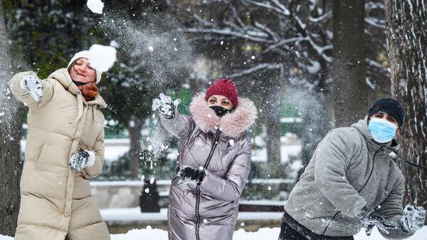 Прохожие играют в снежки на одной из улиц в Баку во время снегопада