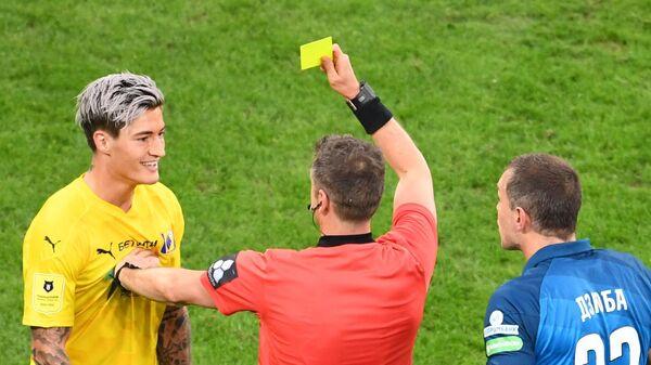 Главный судья Алексей Матюнин показывает желтую карточку игроку Ростова Матиасу Норманну