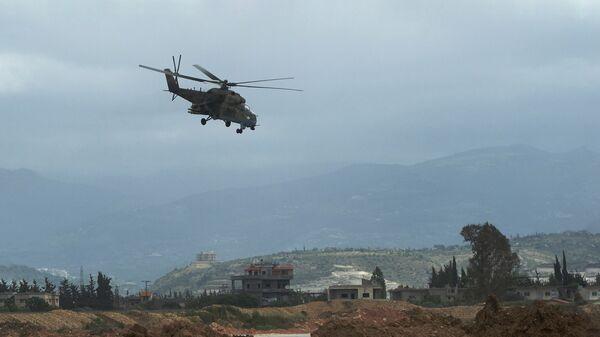 Российский вертолет Ми-35 совершает полет у авиабазы Хмеймим в Сирии