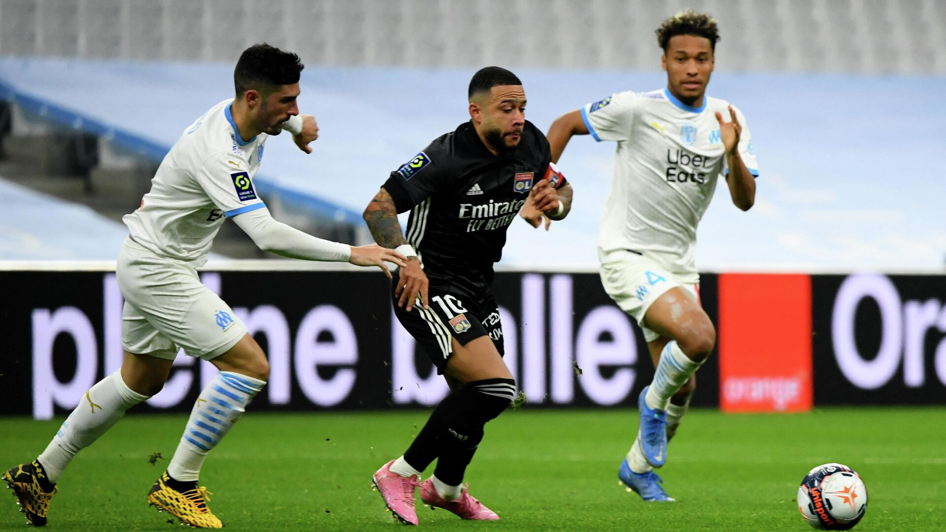 Lyon's Dutch forward Memphis Depay (C) fights for the ball during the French L1 football match between Olympique de Marseille (OM) and Olympique Lyonnais (OL) at the Velodrome stadium in Marseille on February 28, 2021. (Photo by CLEMENT MAHOUDEAU / AFP) - РИА Новости, 1920, 01.03.2021