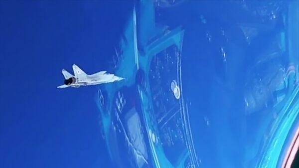 Истребитель МиГ-31 во время перехвата самолета-нарушителя противника, пытавшегося прорваться в воздушное пространство страны на большой высоте и сверхзвуке, в рамках учений в Арктике