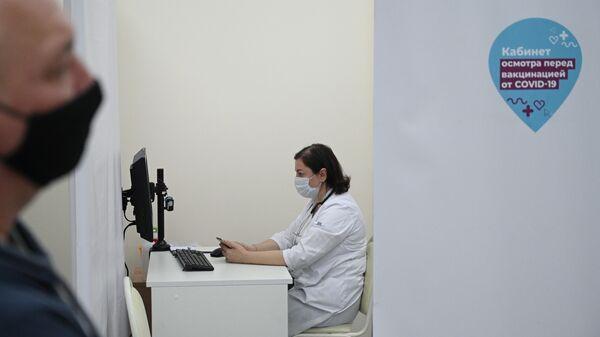 Медицинский работник в мобильном пункте вакцинации от COVID-19  в торговом центре Тройка в Москве