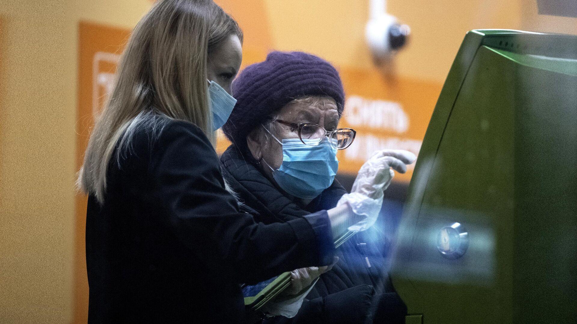 Сотрудница в отделении Сбера помогает женщине у банкомата - РИА Новости, 1920, 09.02.2021