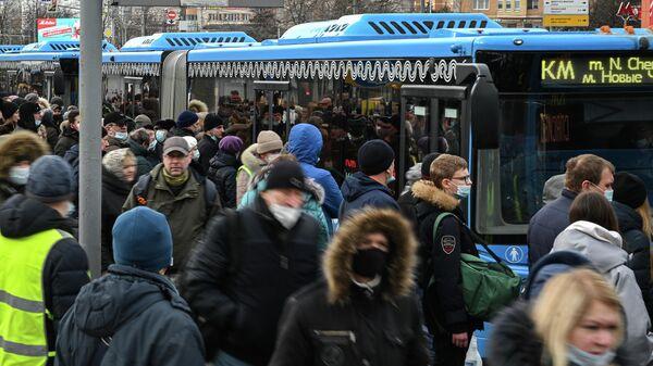 Пассажиры на остановке бесплатных автобусов КМ у станции метро Беляево