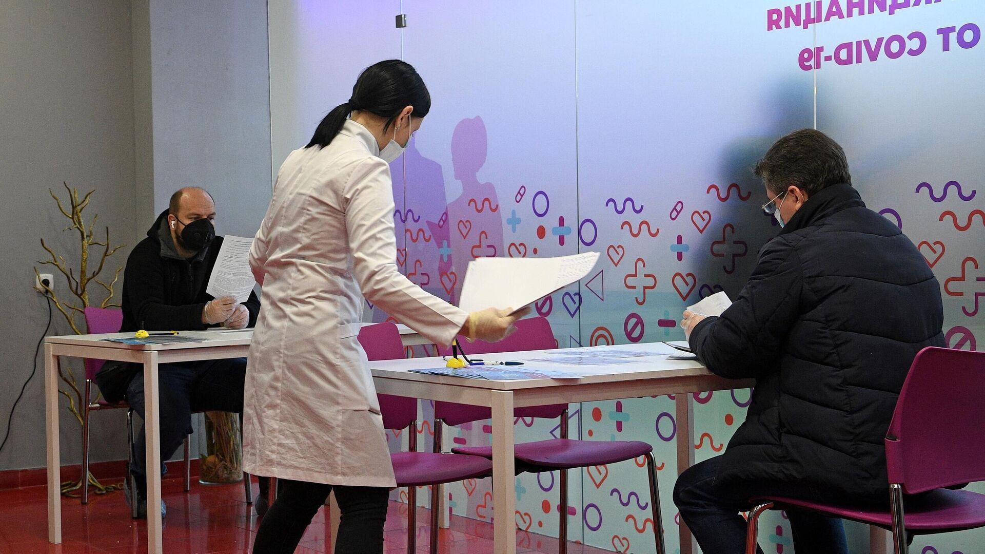 Мужчины заполняют анкеты перед вакцинацией от COVID-19 в пункте вакцинации в торговом центре РИО в Москве - РИА Новости, 1920, 23.03.2021