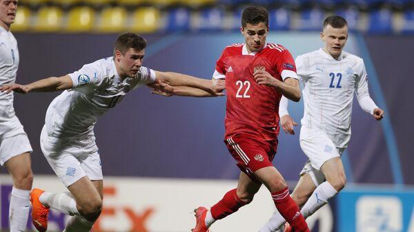 Игрок молодежной сборной Исландии Ари Лейфссон, игрок молодежной сборной России Арсен Захарян и игрок молодежной сборной Исландии Кольбейнн Тордарсон (слева направо) в матче 1-го тура группового этапа чемпионата Европы по футболу 2021 среди молодежных команд между сборными России и Исландии.