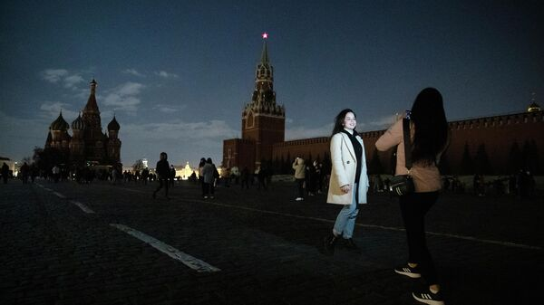 Девушки фотографируются на Красной площади в Москве во время экологической акции Час Земли