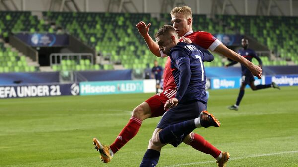 Игрок сборной России Павел Маслов (слева) и игрок сборной Франции Адриен Трюффер в матче молодежного чемпионата Европы по футболу между сборными России и Франции.