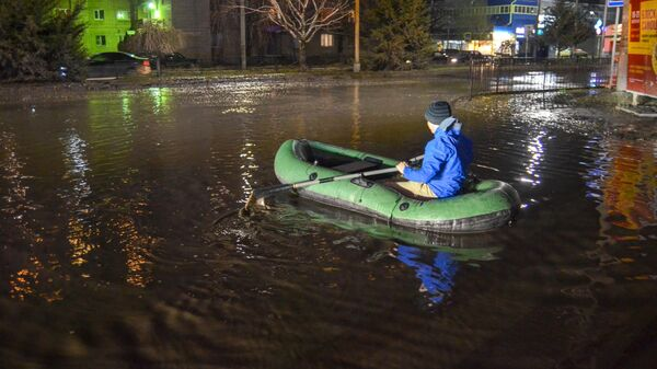 Жители города Таганрога перебираются через лужу на надувной лодке