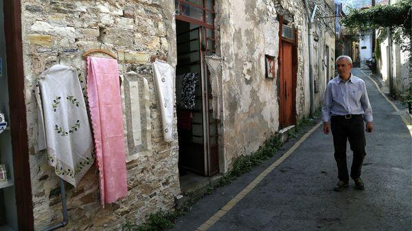 Мужчина проходит мимо магазинов с кружевными изделиями в деревне Лефкара