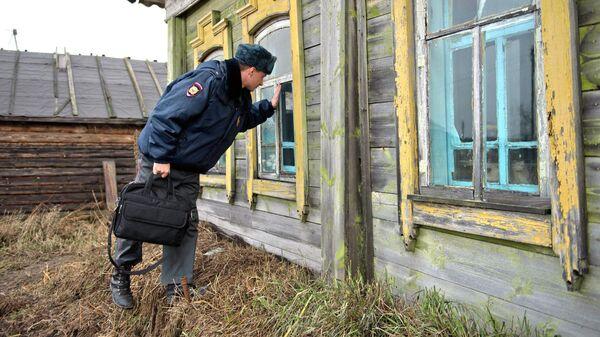 Участковый уполномоченный полиции во время осмотра дома