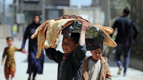 Афганский мальчик несет хлеб в Кабуле