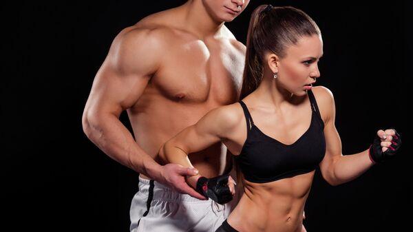 Молодой человек и девушка, занимающиеся фитнесом