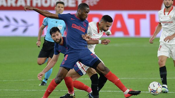 Atletico Madrid's French midfielder Geoffrey Kondogbia (L) challenges Sevilla's Moroccan forward Youssef En-Nesyri during the Spanish League football match between Sevilla FC and Club Atletico de Madrid at the Ramon Sanchez Pizjuan stadium in Seville on April 4, 2021. (Photo by CRISTINA QUICLER / AFP)