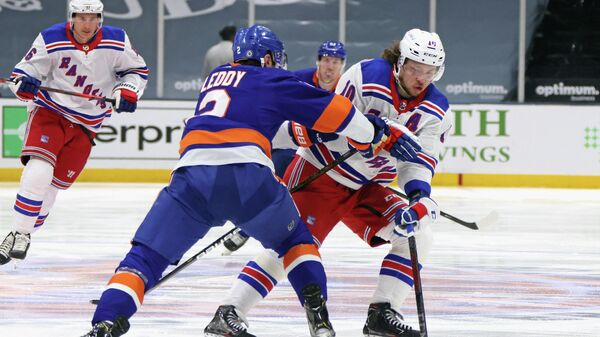 UNIONDALE, NEW YORK - APRIL 09: Artemi Panarin #10 of the New York Rangers carries the puck in on Nick Leddy #2 of the New York Islanders at Nassau Coliseum on April 09, 2021 in Uniondale, New York.   Bruce Bennett/Getty Images/AFP (Photo by BRUCE BENNETT / GETTY IMAGES NORTH AMERICA / Getty Images via AFP)