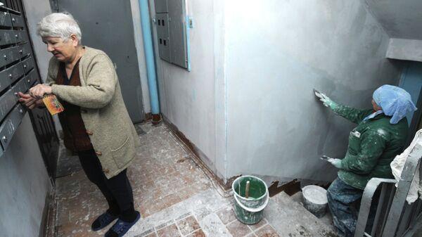 Жительница дома вынимает почту в подъезде, где маляр работает на ремонте лестничных пролетов